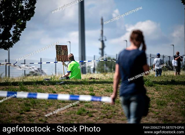 """27 June 2020, North Rhine-Westphalia, Gelsenkirchen: A man holds up a sign in the air that says """"""""Our virus is called a supervisory board"""