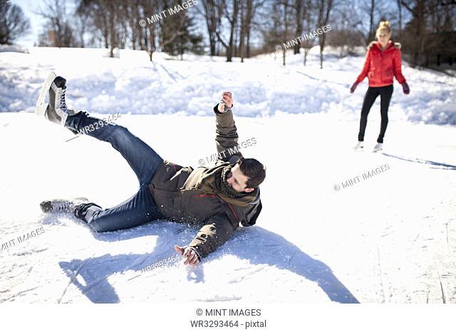 Caucasian man falling while ice skating on frozen lake