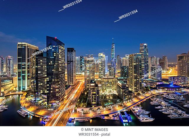 Cityscape of Dubai, United Arab Emirates at dusk, with illuminated skyscrapers and the marina in the foreground