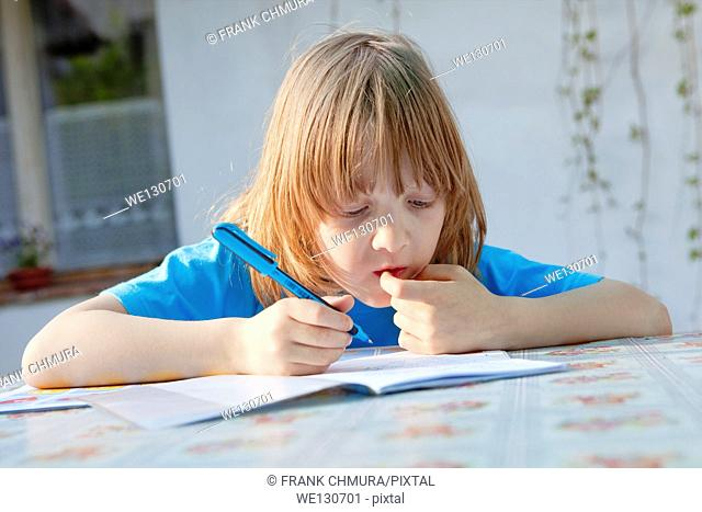 Boy with long blond hair doing homework outdoors
