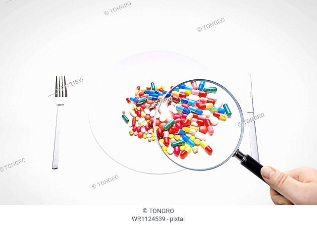 different color pills and capsules on a food plate