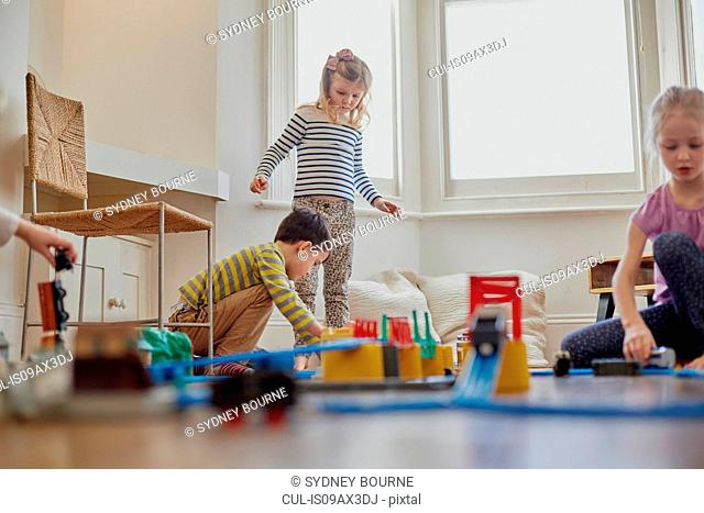 Young children playing with toy train set