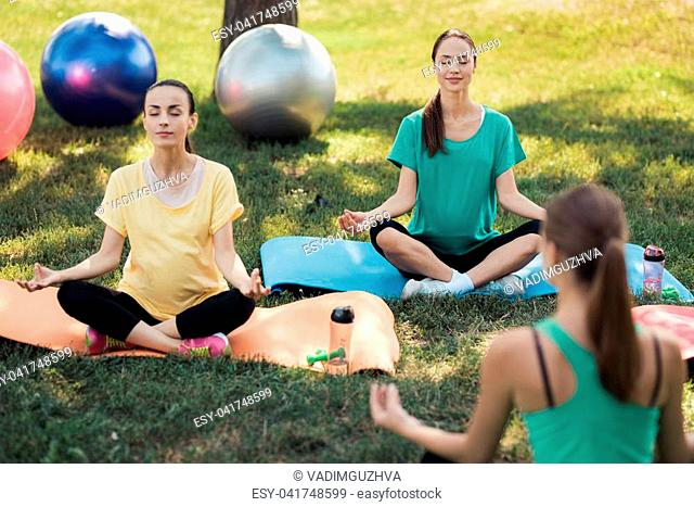 Pregnancy yoga. Three pregnant women came to the yoga class. In front of them is a female coach. They all sit in the lotus position