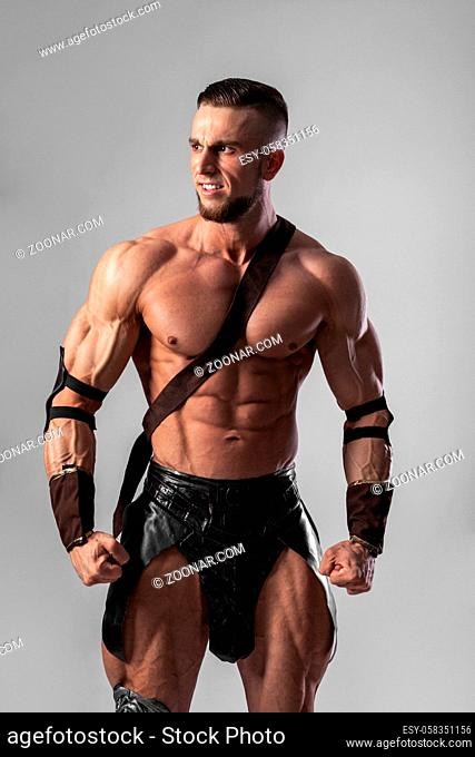 Half length portrait of young handsome muscular man gladiator in armour posing, concept of masculinity, determination, strength
