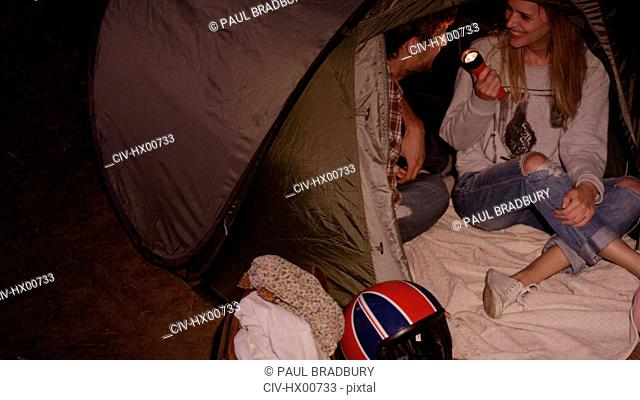 Young couple with flashlight inside camping tent
