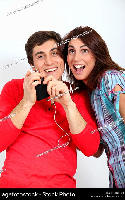 Couple having fun listening to music player