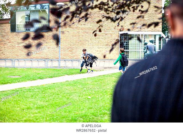 Schoolboys playing at lawn