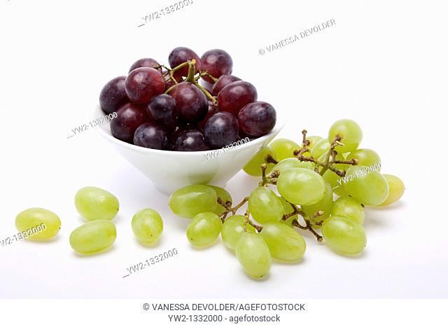 Studio photograph of a white bowl with blue and white grapes on a white background