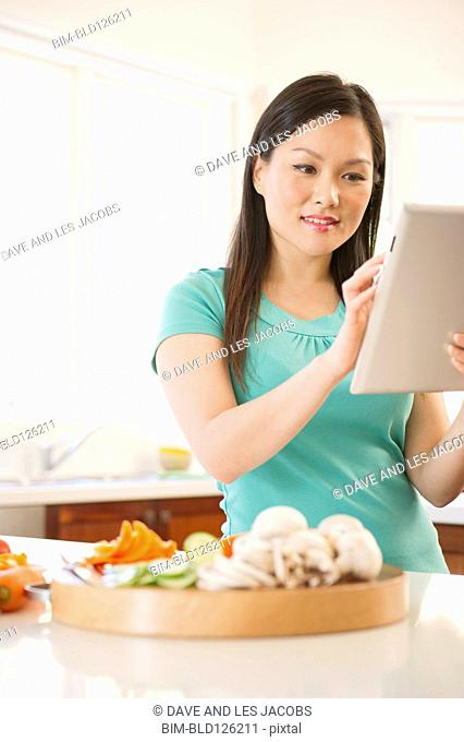 Chinese woman with digital tablet in kitchen