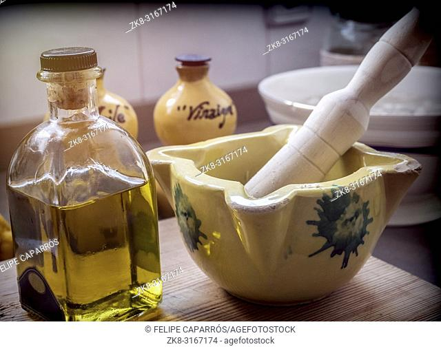 Traditional ceramic mortar next to a bottle of olive oil in a kitchen, traditional cooking utensils