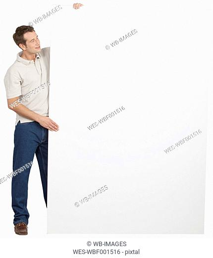 Mid adult man holding poster, smiling