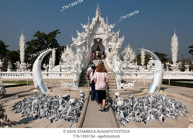 tourists entering the amazing white temple Wat Rong Khun in Chiang Rai, Thailand