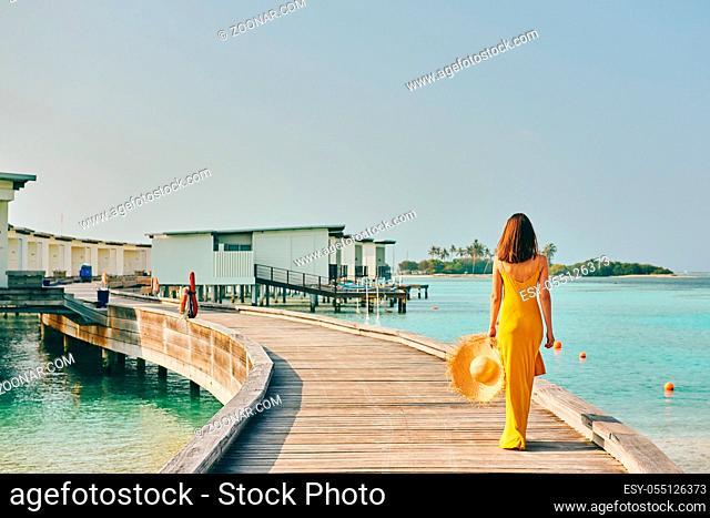 Woman in dress walking on tropical beach boardwalk. Summer vacation at Maldives