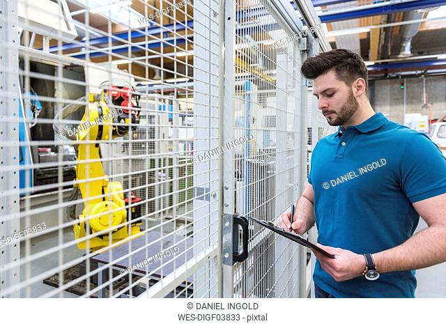 Man with clipboard standing at industrial robot in modern factory