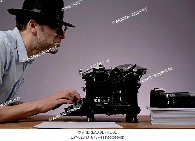 Agent with an old type writer and a vintage camera in a dark office