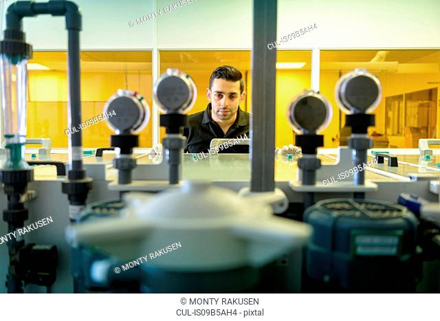 Worker operating circuit board processing machine in electronics factory