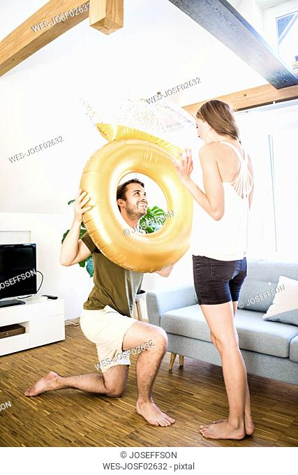 Smiling man looking at girlfriend through large inflatble ring at home