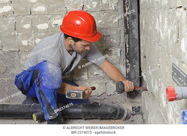 An electrician, systems mechanic for sanitary engineering, heating and air conditioning, installing a sewer pipe, driving a slot for a sewer pipe, refurbishment