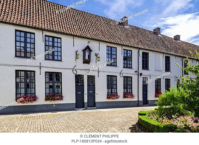 17th century white beguines' houses in courtyard of the Beguinage of Oudenaarde, East Flanders, Belgium
