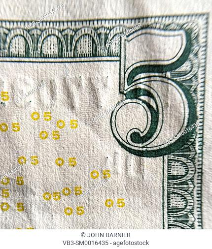 Closeup of the corner of an American $5 bill