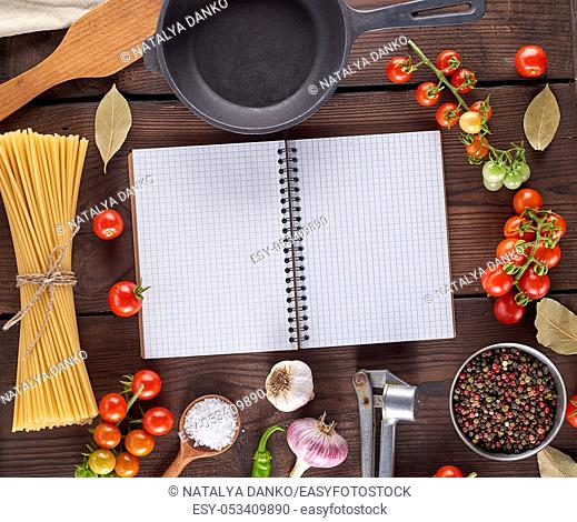 open blank notebook with white sheets, raw long paste and ingredients for cooking, top view