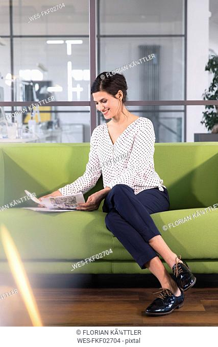 Businesswoman sitting on a couch in the office, looking at documents