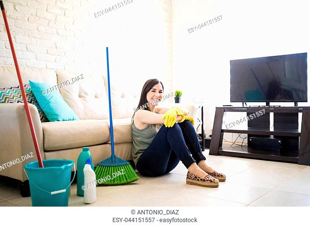 Adorable young woman feeling blessed after completing house chores sitting in living room with rest of couch