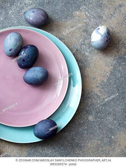 pink and blue plate with Easter eggs hand-made robotic concrete background flat lay
