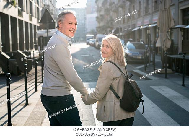 Senior couple walking on street in city