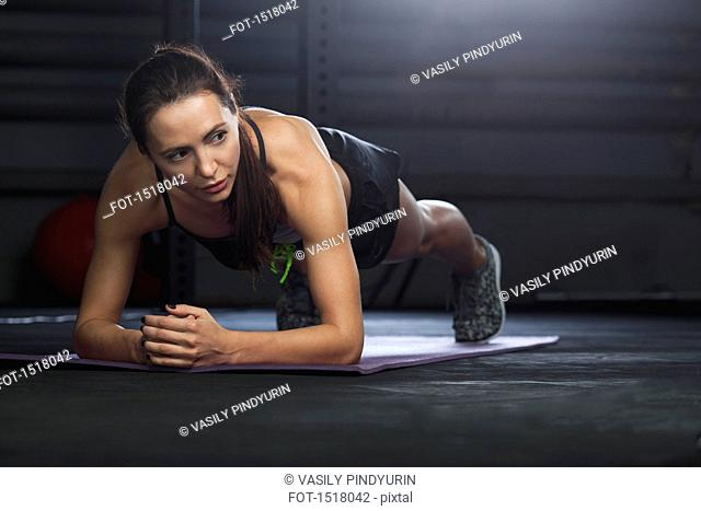 Woman looking away while exercising on mat at gym