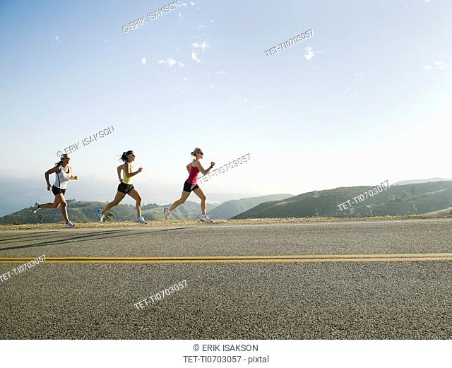 Runners training on side of a road