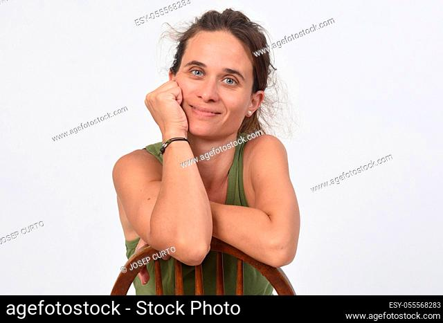 portrait of a 40 year old woman without makeup on white background, sitting on a chair and looking at camera and hand on face,