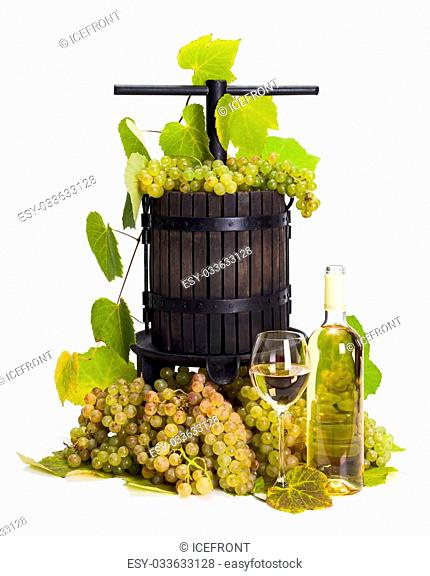 Traditional manual grape pressing utensil with wine and white grape bunch