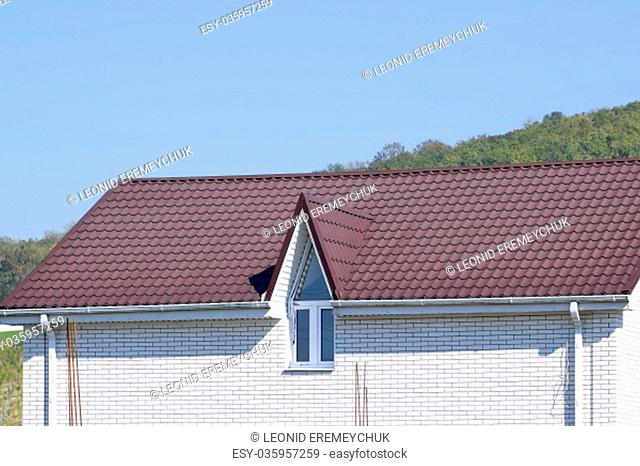 House with plastic windows and a brown roof of corrugated sheet. Roofing of metal profile wavy shape on the house with plastic windows