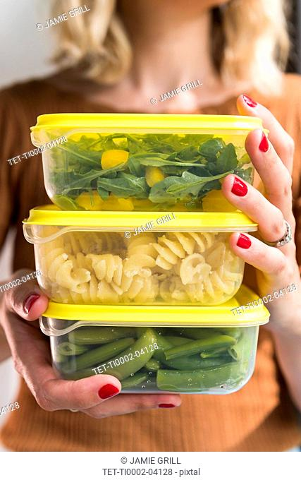Woman holding stack of food in plastic containers