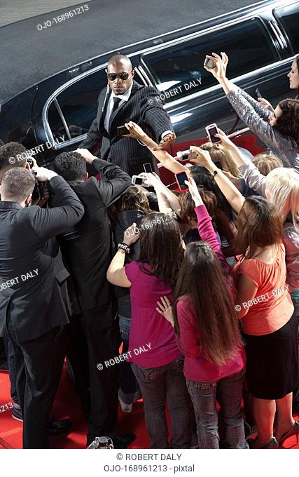 Celebrity emerging from limo toward paparazzi