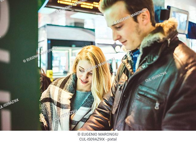 Young couple buying train tickets from ticket machine