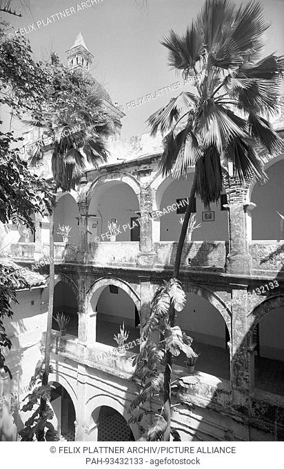 Narrow three-storey courtyard of the college, with arcades on pilasters. in the..Background a tower of the church, Cartagena (Bolivar), Colombia, 1958