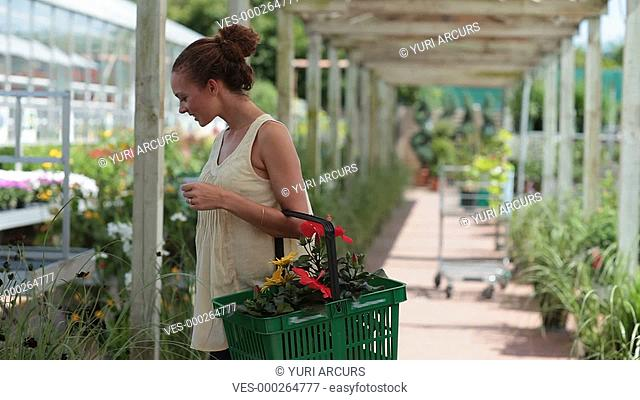 Young woman choosing the right kind of landscaping plants at her local gardening centre