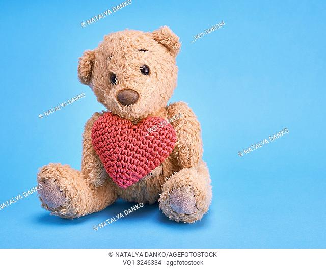 little teddy bear holding a red heart on a blue background