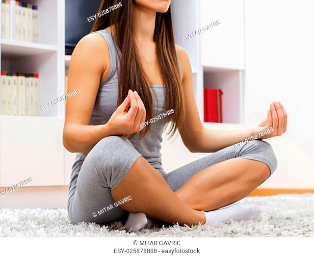 Young woman practicing yoga meditation at home. Fit caucasian female in sportswear exercising.Healthy lifestyle