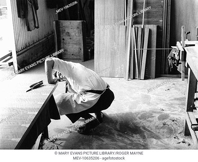 Man at work at the Gordon Russell factory, Broadway, Worcestershire. Sir Gordon Russell set up the business to make furniture in the William Morris arts and...
