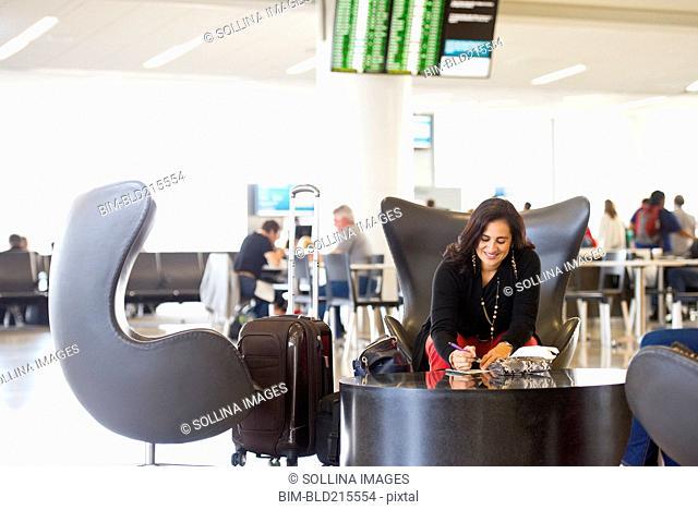 Hispanic businesswoman writing in airport waiting area