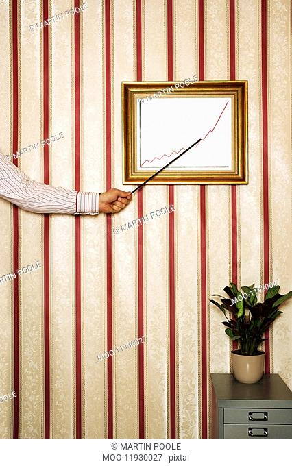 Man pointing to framed graph on office wall close-up of arm and hand