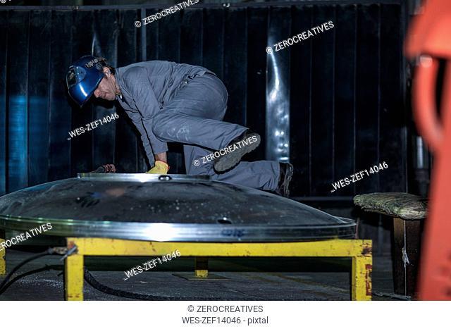 Worker wearing welding mask in factory