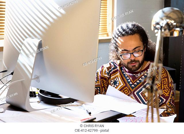 Focused creative businessman reading paperwork at computer in office