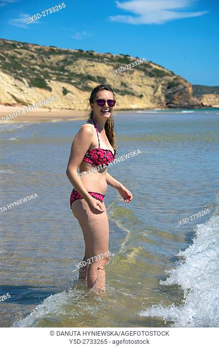 young woman on vacation at the beach, here Salema beach, Algarve, Portugal, Europe