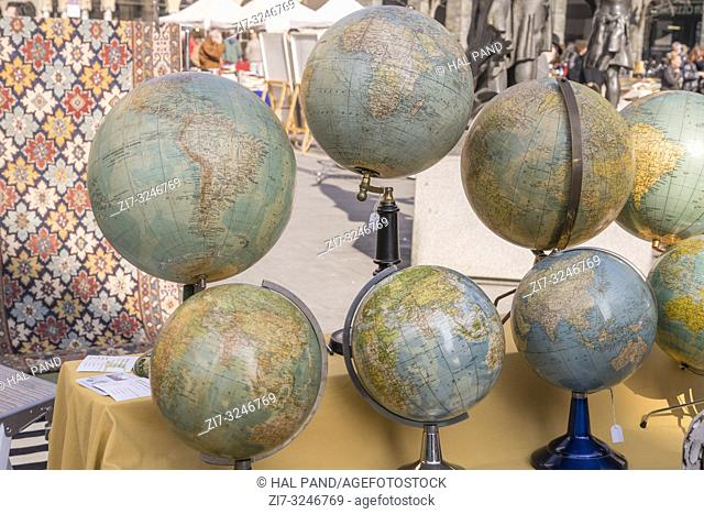 group of vintage spherical globes on sale at street market, shot in bright winter light at Cremona, Lombardy, Italy