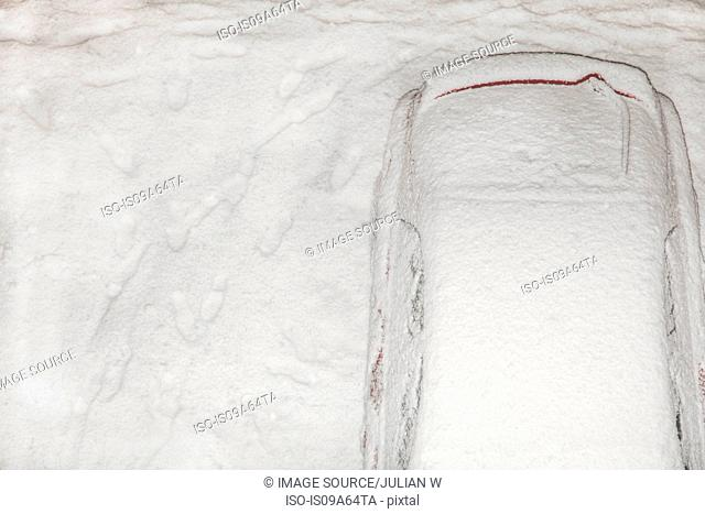 Snow-covered car in driveway