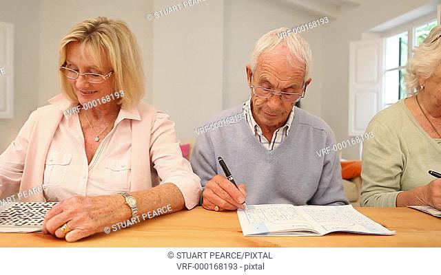 Five Seniors doing crossword puzzles